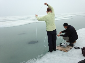 Tara and Dr. Jim McClelland collect water samples through a hole in the sea ice